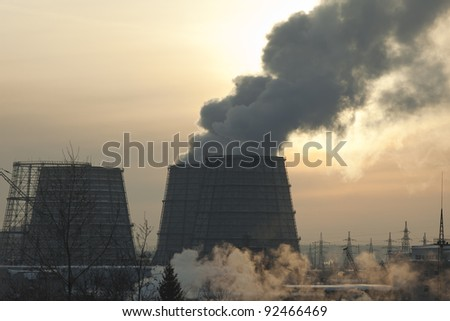 energy station with smoke at winter sunset - stock photo