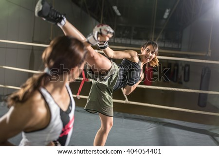 energy women practicing body combat attack in boxing ring - stock photo