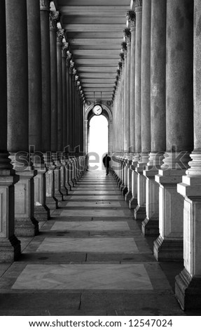 Enfilade of columns and lonely human silhouette. Black and white - stock photo