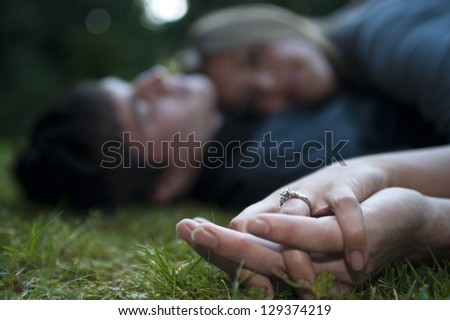 Engaged couple embracing, focus on ring - stock photo
