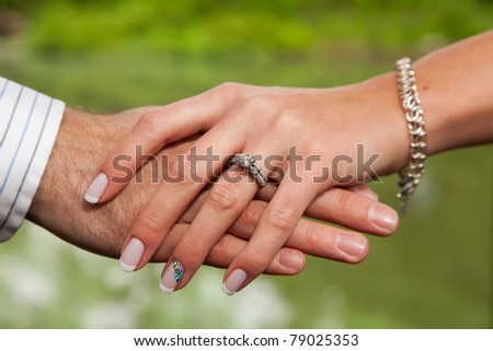 Engaged couple hold hands showing the new diamond ring on the woman's finger - stock photo