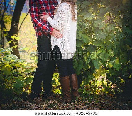Engaged couple hugging with fall background.