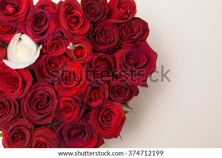 Engagement ring lies on beautiful bouquet of roses. Red flowers like a heart.