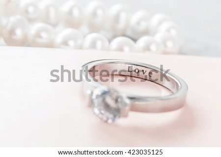 Engagement ring on a pastel pink box, selective focus, inscription love on the inside - stock photo