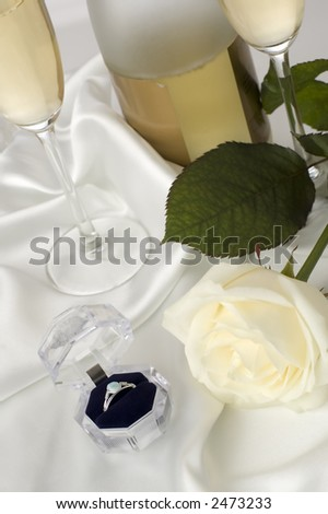 engagement ring with white rose and champagne in background