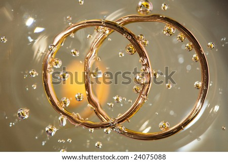 engagement rings, sunk in water - stock photo