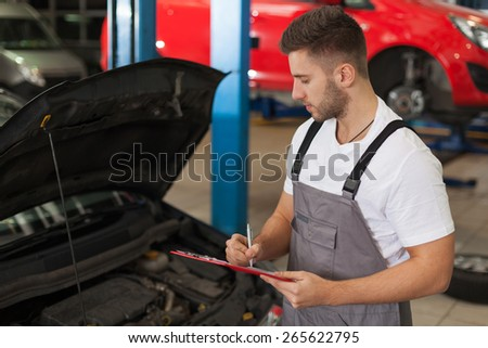 Engine quality control. Focused mechanic in auto repair shop looking at an engine and writing something on a clipboard