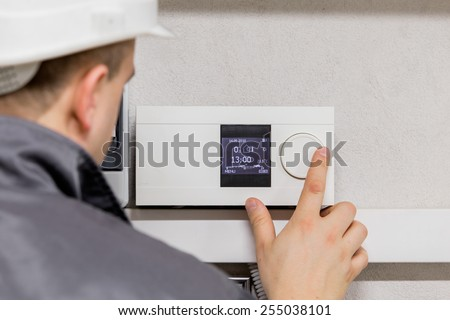 Engineer adjusting thermostat for efficient automated heating system - stock photo
