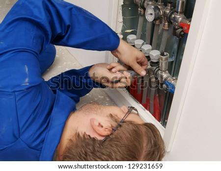 Engineer adjusting under floor heating valves - stock photo