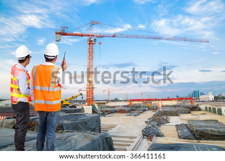 Engineer and foreman looking at crane construction with talking on the walkie-talkie for controlling crane loading at construction site - stock photo