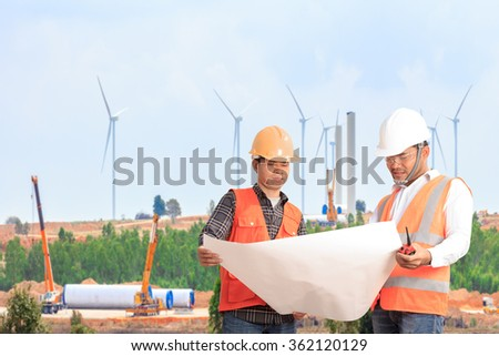 Engineer and Foreman looking to plan for control working at wind turbine power generator station installation site - stock photo