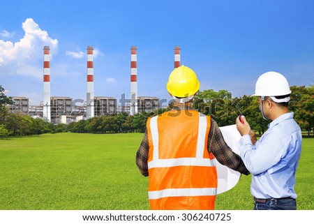 Engineer and foreman use radio communication for command working at modern thermal power plants and electric high voltage towers with green park ecology - stock photo
