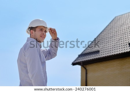 Engineer, architect or building inspector standing in his hardhat checking a roof on a new build house against a blue sky - stock photo