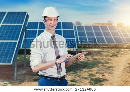 Engineer at solar power station with solar panel tablet checks. Practical lessons on renewable energy power plants. - stock photo