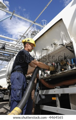 engineer attaching pipeline nozzle inside oil-refinery awaiting oil tanker - stock photo
