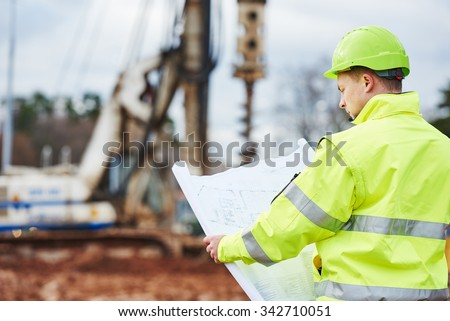 engineer builder with blueprint plan at construction site - stock photo