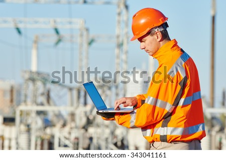 engineer builder with laptop computer at construction site near power plant - stock photo