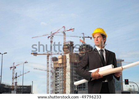 Engineer carrying some paper rolls with construction site on the background - stock photo