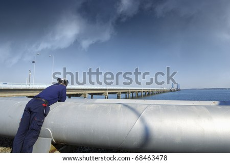 engineer checking long pipeline construction leading to refinery, dark mclouds on horizon - stock photo
