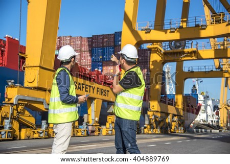 Engineer control Container Cargo freight ship with working crane loading bridge in shipyard - stock photo