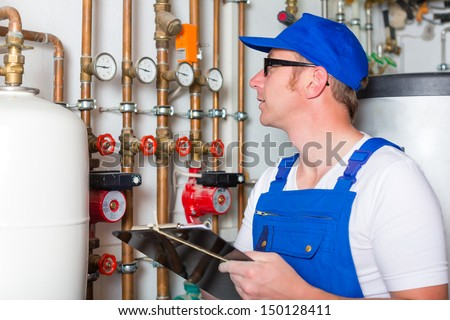 Engineer controlling the heating pipes at the boiler room - stock photo