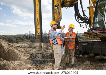 Engineer Directs Construction Worker - stock photo