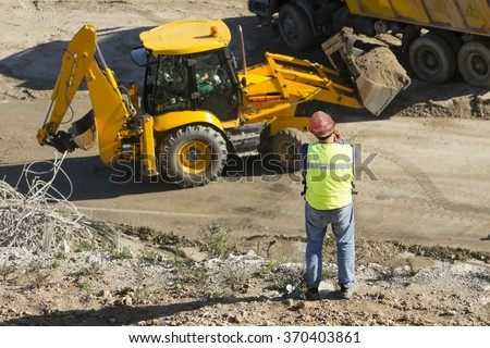 engineer foreman in highway construction site with excavators and trucks - stock photo