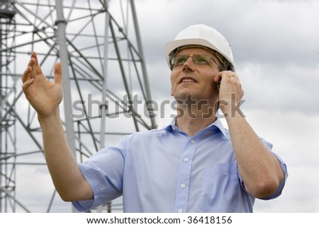 Engineer gesturing while talking on cell phone on construction side - stock photo