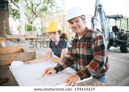 Engineer going over blueprints with a student on the construction site.   - stock photo