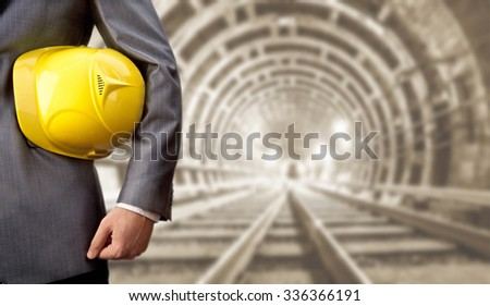 engineer hand hold yellow helmet for workers security against the background of an underground mine with arc legs and rails for trolleys with coal in perspective Empty space for inscription or objects - stock photo