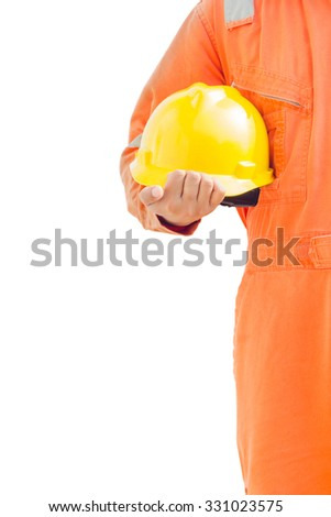 engineer hand holding yellow helmet for workers against background oil and gas process - stock photo
