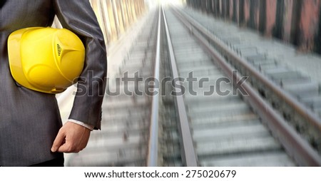 engineer hand holding yellow helmet for workers security against background of an underground mine with arc legs and rails for trolleys with coal in perspective Transportation concept  - stock photo