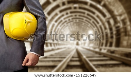 engineer hand holding yellow helmet for workers security against the background of an underground mine with arc legs and rails for trolleys with coal in perspective  - stock photo