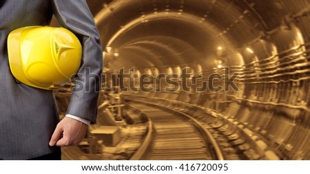 engineer hand holding yellow helmet for workers security against the background of an underground mine with arc legs and rails for trolleys with coal in perspective. - stock photo