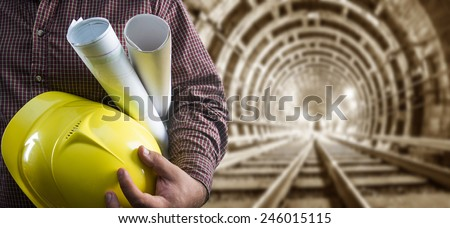 engineer hand holding yellow helmet for workers security and blueprint paper plan against the background of an underground mine with arc legs and rails for trolleys with coal in perspective - stock photo