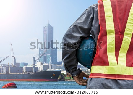Engineer holding a blue helmet for the safety of workers on the background of a port with cranes and containers - stock photo