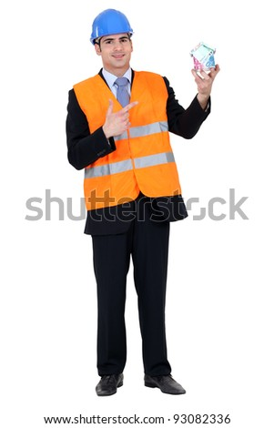 Engineer holding a house built of money - stock photo