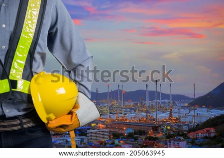 Engineer holding a yellow helmet for the safety of workers on the background oil refinery. Beautiful sky at dawn - stock photo