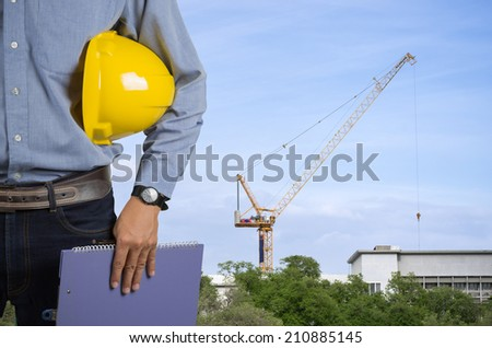 Engineer holding a yellow helmet for the safety of workers on the background stock port with cranes and containers. - stock photo