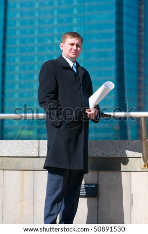 Engineer holding drawing on skyscrapers background - stock photo