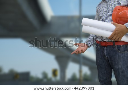 Engineer holding helmet and blueprint in hands over blurred construction background, security  - stock photo