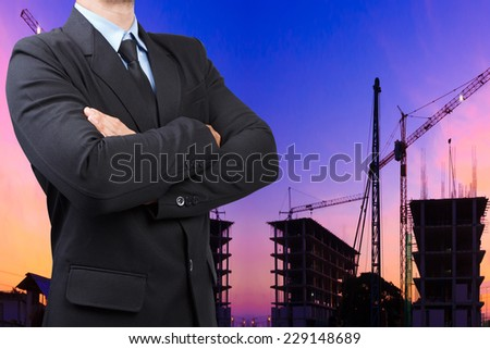engineer holding helmet and blueprints against silhouette of crane and building construction and beautiful sunset sky    - stock photo