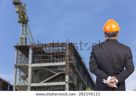 engineer holding orange helmet for workers security on contruction background