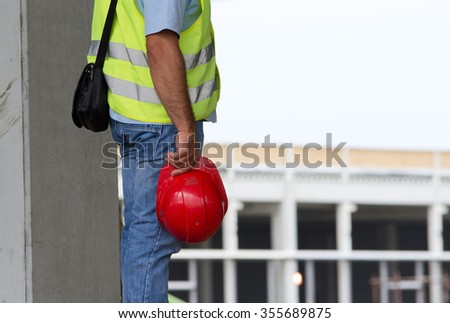 Engineer holding red helmet in hand and supervising works on construction site - stock photo