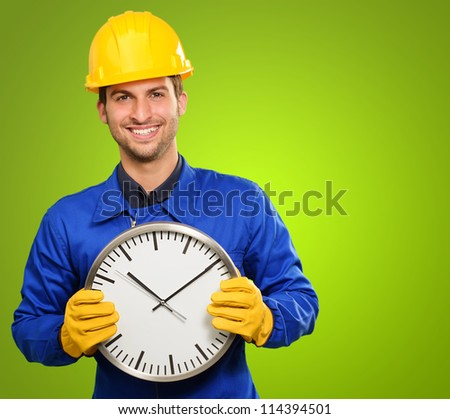 Engineer Holding Wall Clock On Green Background - stock photo