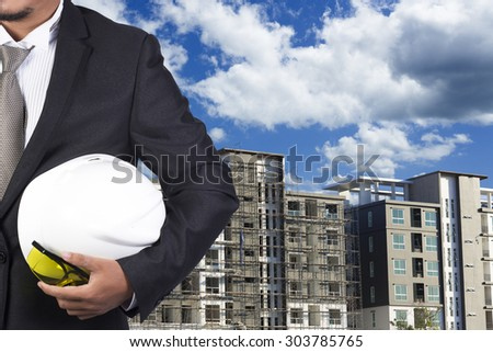 engineer holding white helmet for workers security on background of new highrise apartment buildings and construction background of blue sky - stock photo