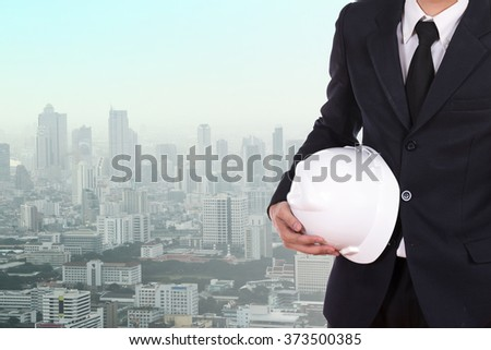 engineer holding white helmet with city background - stock photo