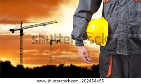 engineer holding yellow helmet for workers - stock photo