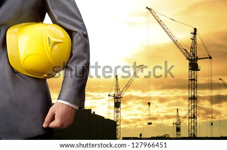 engineer holding yellow helmet for workers security on background of  new highrise apartment buildings and construction cranes on background of evening sunset cloudy sky Silhouette Crane lifts load