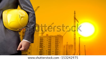 engineer holding yellow helmet for workers security on background of new highrise apartment buildings and construction cranes on background of evening sun set cloudy sky Silhouette Crane lifts load - stock photo